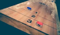 Vintage shuffle board game with red and blue disc on wooden shuffle table. Shuffleboard table game with selective focus.