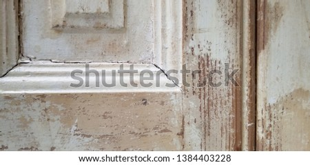 Vintage shutter with distressed look. White paint has chipped look that shows bare wood.  The picture shows only one corner of the shutter.