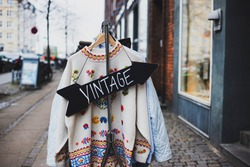 Vintage sign with a background of different vintage clothing on a street. White vintage sweater with embroidered flowers.