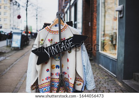 Vintage sign with a background of different vintage clothing on a street. White vintage sweater with embroidered flowers.   Foto stock ©