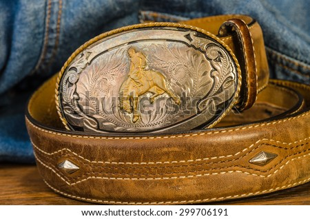 Vintage silver buckle with cowboy on bucking bronc.  Leather belt with studs against blue denim work shirt background. - Shutterstock ID 299706191