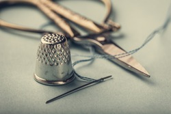 Vintage silver metal thimble and needle, scissors on blue background