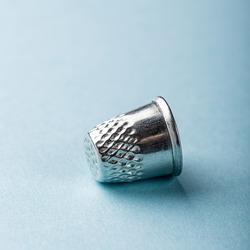 Vintage silver metal thimble on blue background
