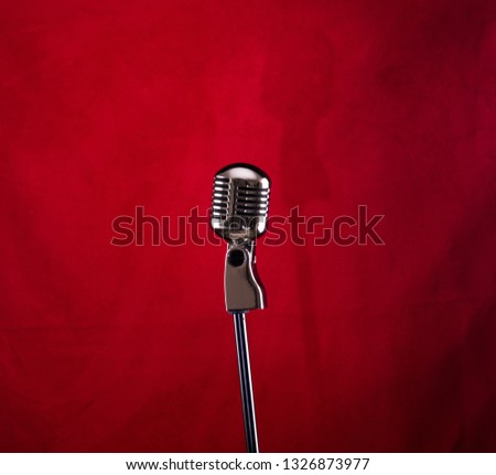 vintage silver microphone on a red stage #1326873977