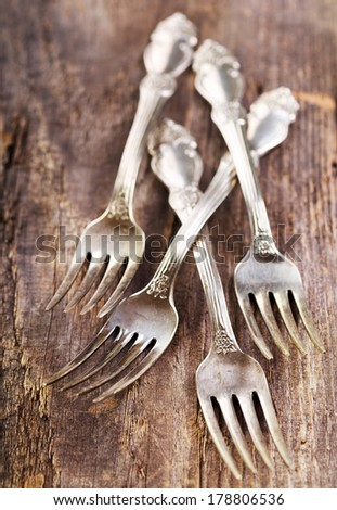 Vintage silverware forks lying on rustic wooden table