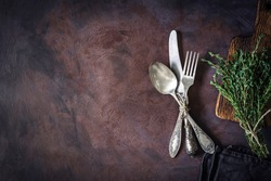 Vintage silverware on a dark textile and bunch of fresh thyme on dark rusty background. Top view, copy space for text.