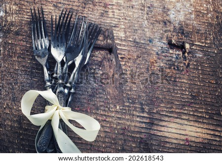 Vintage silverware on aged wooden background. Selective focus, horizontal.