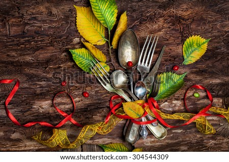 Vintage silverware on rustic wooden background with autumn decoration Organic Food concept. Vintage cutlery, antique silverware, fork, knife