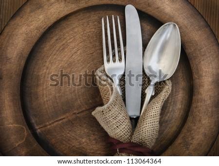 Vintage silverware on rustic wooden plate #113064364