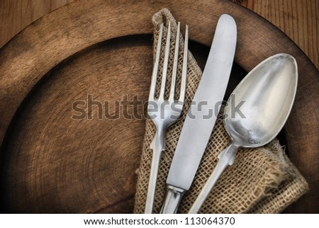 Vintage silverware on rustic wooden plate