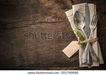 Vintage silverware with a twig of rosemary and empty tag on rustic wooden background #305740088