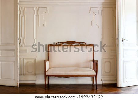 Vintage sofa, armchair in empty room with stucco elements wall background. Living room with antique stylish chair on wall in the middle of two old doors. bas-relief stucco mouldings roccoco elements