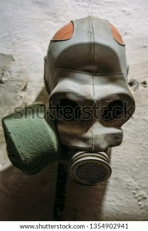 Vintage Soviet Gas Mask on white wall in bomb shelter, close up