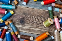 Vintage spools with colored threads on old tailoring table with copy space