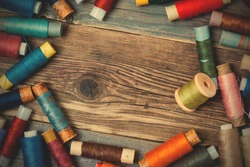 Vintage spools with colored threads on old tailoring table with copy space. instagram image filter retro style