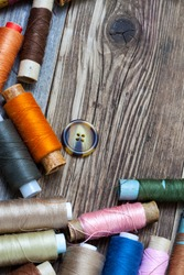 Vintage spools with multi colored threads and old button on old tailoring table