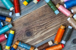 Vintage spools with multi colored threads on old tailoring table with copy space