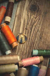 Vintage spools with varicolored threads and old button on old tailoring table. instagram image filter retro style