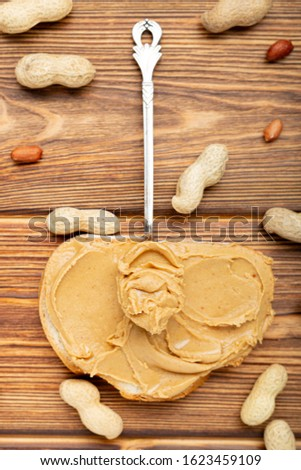 Vintage spoon with creamy peanut butter on a peanut butter bread. Peanuts in the shell and peeled peanuts on brown wooden table. Flat lay of peanut paste for cooking breakfast.Vegan food concept