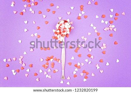 Vintage spoon with small pink, white, red sweet hearts on pastel Violet background. Flat lay stale. Valentine's Day celebration concept. Romantic mood. #1232820199