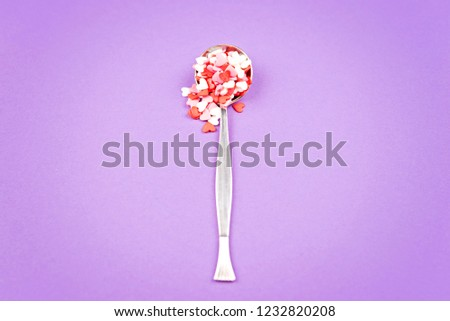 Vintage spoon with small pink, white, red sweet hearts on pastel Violet background. Flat lay stale. Valentine's Day celebration concept. Romantic mood. #1232820208