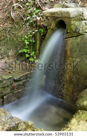 vintage spring in forest with bricks reservoir