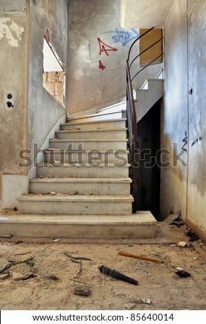 Vintage staircase and dirty floor in abandoned building interior.