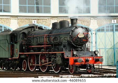 Vintage steam engine on work on railway before turntable