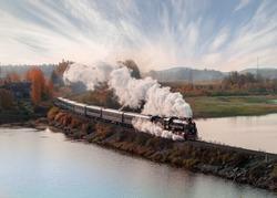 Vintage steam locomotive train in the autumn landscape.
