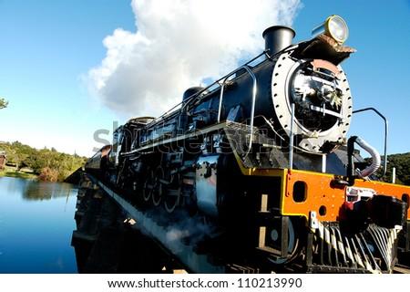 Vintage steam train crossing a river