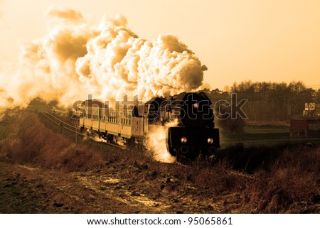 Vintage steam train passing through countryside, wintertime