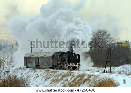 Vintage steam train passing through snowy countryside