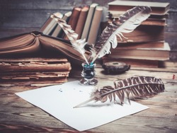 Vintage still life. Old books, ink, feathers on a wooden background. Close up. Selective focus. Retro toning.