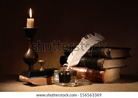 Vintage still life. Old inkstand near lighting candle and books