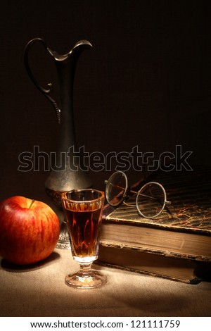 Vintage still life with apple and drink near old book on canvas surface