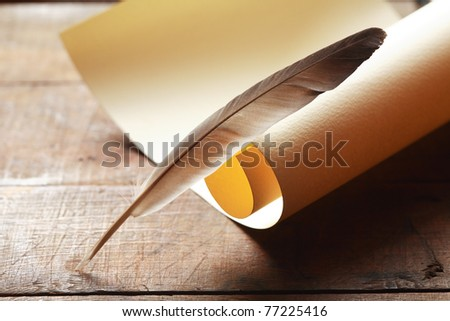 Vintage still life with blank scroll and quill on wooden surface