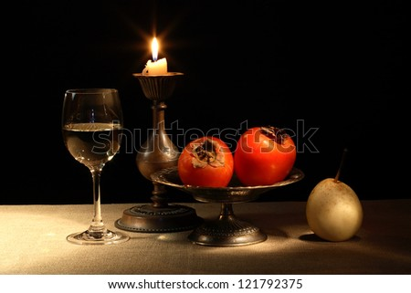 Vintage still life with fruits in bowl and wineglass near lighting candle