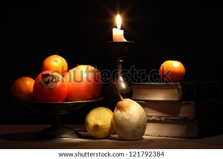 Vintage still life with fruits in bowl near old books and lighting candle