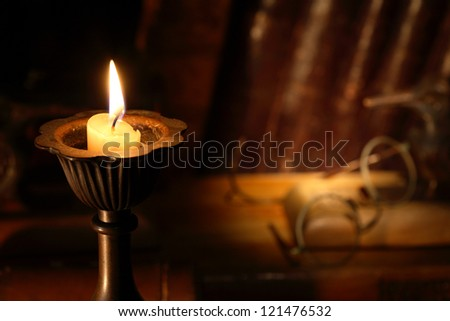 Vintage still life with lighting candle on background with old spectacles and books