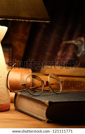 Vintage still life with old spectacles on book near desk lamp