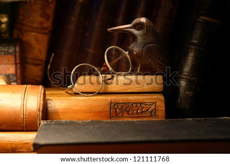 Vintage still life with old spectacles on desk set against books