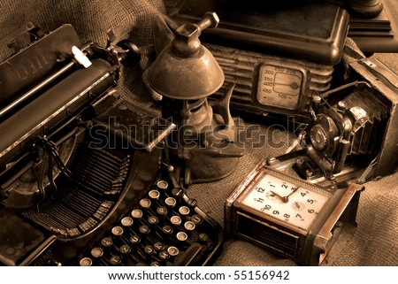 Vintage still life with old typewriter, retro camera and radio receiver in brown colors