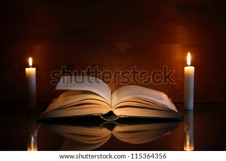 Vintage still life with open old book near two lighting candles - stock photo