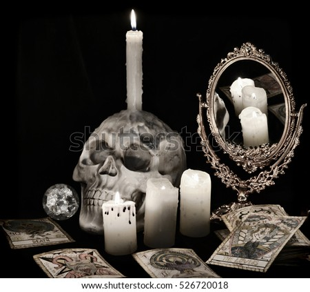 Vintage still life with scary skull, mirror, burning candles and the ...