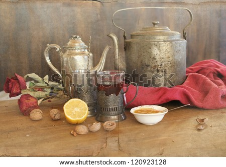 vintage still life with teapot's, cups in glass-holders, lemon and honey