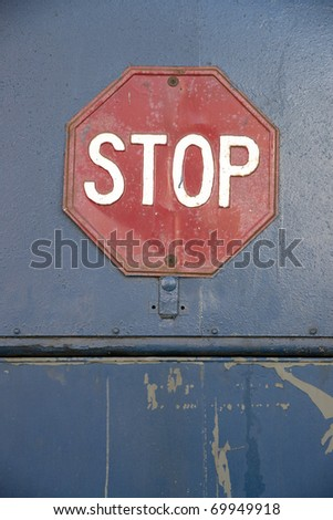 vintage Stop sign on blue wall - stock photo