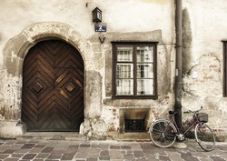Vintage street scene with large wooden door and bicycle, in the old town in Krakow, Poland.