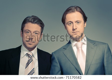 Vintage studio portrait of two young business men. Proud. Relaxed. Happy. Lucky. Duo.