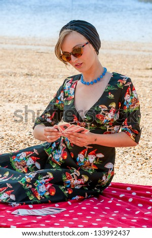 Vintage style beauty seated on red blanket enjoying game of cards in the summer sunshine on beach