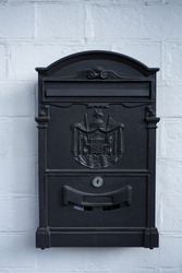 Vintage style black letterbox mounted on a white painted wall